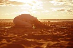 La giovane bella siluetta esile della donna pratica l'yoga sul beac Fotografie Stock Libere da Diritti
