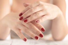 La giovane bellezza con rosso ha dipinto i chiodi, molto rilassati Fotografia Stock Libera da Diritti