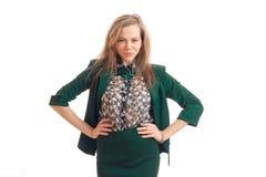 La giovane bionda sexy in un vestito verde sembra lo sguardo fisso abile e tiene le sue mani dai lati Immagini Stock