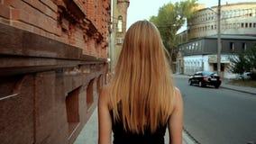 La giovane bionda snella cammina sulla città archivi video