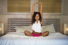 La giovane camera da letto ispanica nera attraente e felice della donna a casa che fa la meditazione di joga ed il rilassamento d immagine stock