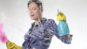 La giovane casalinga ha lavato la finestra con uno spruzzo, un panno e un detersivo Grande vetro in schiuma Concetto di lavoro do archivi video