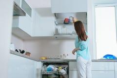 La giovane casalinga mette i piatti puliti dalla lavastoviglie sugli scaffali dell'armadio da cucina, retrovisione immagine stock libera da diritti