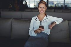 La giovane chiamata aspettante femminile allegra sul telefono cellulare durante il lavoro irrompe l'interno moderno della caffett Fotografia Stock