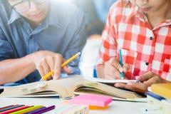 La giovane città universitaria degli studenti aiuta l'amico che prende e che impara Immagine Stock