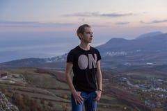 La giovane condizione attraente dell'uomo sulla cima delle montagne esamina la distanza immagine stock