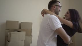 La giovane coppia è occupata muoversi La progettazione di nuova casa Il marito alza la sua moglie e gira Fra gli scaffali di stock footage
