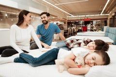 La giovane coppia adorabile sta sedendosi sul materasso accanto ai bambini addormentati in negozio di mobili Fotografia Stock
