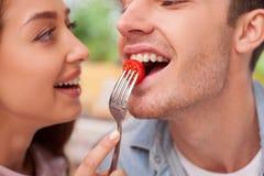 La giovane coppia amorosa allegra sta mangiando dentro Immagini Stock Libere da Diritti
