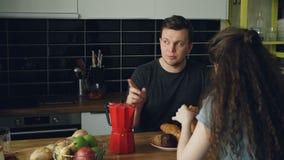 La giovane coppia caucasica che si siede alla tavola in cucina moderna a casa che dicussing qualcosa, donna riccia sta sedendosi  video d archivio
