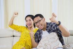 La giovane coppia celebra la loro vittoria del gruppo Immagini Stock
