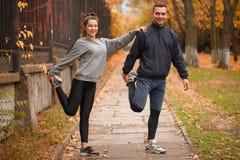 La giovane coppia che allunga la gamba muscles la condizione in un parco Fotografie Stock Libere da Diritti