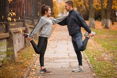 La giovane coppia che allunga la gamba muscles la condizione in un parco e l'esame reciprocamente Immagini Stock Libere da Diritti