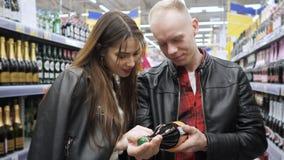 La giovane coppia compra i prodotti in un supermercato, sceglie una bottiglia dell'etichetta della lettura del vino archivi video