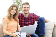 La giovane coppia degli studenti utilizza un computer portatile che si siede sul sofà Immagine Stock Libera da Diritti