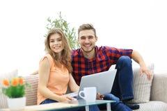 La giovane coppia degli studenti utilizza un computer portatile che si siede sul sofà Immagine Stock