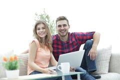 La giovane coppia degli studenti utilizza un computer portatile che si siede sul sofà Immagini Stock Libere da Diritti
