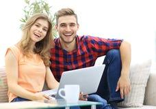 La giovane coppia degli studenti utilizza un computer portatile che si siede sul sofà Fotografie Stock