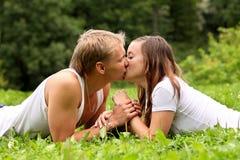 La giovane coppia di amore sta baciando su erba Fotografia Stock Libera da Diritti