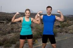 La giovane coppia di sport che posa e che mostra arma sorridere dei muscoli del bicipite felice fotografie stock libere da diritti