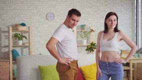 La giovane coppia esamina il loro corpo nello specchio dopo la perdita del peso stock footage