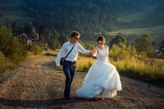 La giovane coppia felice affascinante della persona appena sposata è ridente e tenentesi per mano durante la loro passeggiata lun Immagine Stock