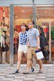 La giovane coppia felice cammina fuori deposito di Uniqlo, Pechino, Cina Fotografia Stock