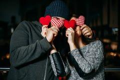 La giovane coppia felice che si copre ` s lo osserva con il cuscino rosso fotografia stock