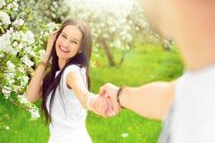 La giovane coppia felice nel giardino con la mela fiorisce Fotografia Stock