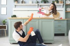 La giovane coppia felice sta divertendosi mentre faceva la pulizia a casa immagine stock libera da diritti