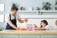 La giovane coppia felice sta divertendosi mentre faceva la pulizia a casa immagine stock