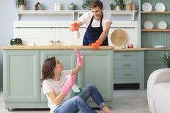 La giovane coppia felice sta divertendosi mentre faceva la pulizia a casa immagini stock libere da diritti
