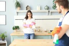 La giovane coppia felice sta divertendosi mentre faceva la pulizia a casa fotografie stock