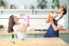 La giovane coppia felice sta divertendosi mentre faceva la pulizia e cantando a casa fotografie stock libere da diritti
