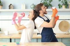 La giovane coppia felice sta divertendosi mentre faceva la pulizia e cantando a casa fotografie stock