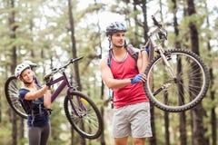 La giovane coppia felice sulle bici che distolgono lo sguardo portanti bikes Immagine Stock