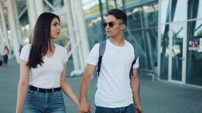 La giovane coppia felice va con bagagli vicino all'aeroporto o alla stazione ferroviaria Il concetto del viaggio, vacanze, feste video d archivio