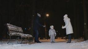 La giovane coppia getta la neve su su una piccola figlia nel parco dell'inverno di sera stock footage