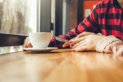 La giovane coppia gode del caffè nel caffè mentre per mezzo di uno smartphone Immagine Stock