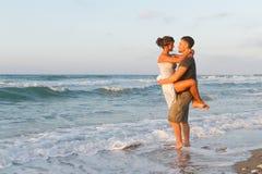 La giovane coppia gode di di camminare su una spiaggia nebbiosa a Immagini Stock