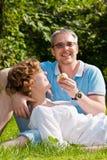 La giovane coppia morde la mela, sedentesi su un'erba Fotografia Stock