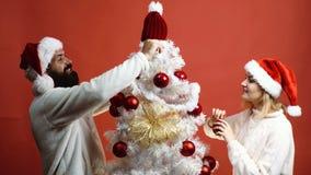 La giovane coppia orna l'albero di Natale su fondo rosso L'uomo barbuto e la bella donna in cappelli del ` s del nuovo anno decor archivi video