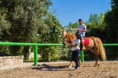 La giovane coppia pratica le lezioni di equitazione Fotografia Stock