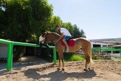 La giovane coppia pratica le lezioni di equitazione Fotografia Stock Libera da Diritti