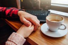 La giovane coppia si tiene per mano e gode del caffè nel caffè mentre per mezzo di un computer portatile Fotografia Stock