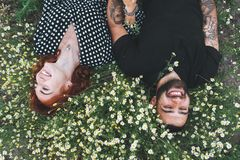 La giovane coppia si trova sul campo con le margherite fotografia stock libera da diritti