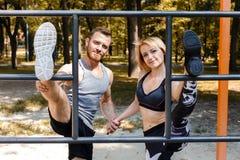 La giovane coppia sportiva sta scaldandosi prima della formazione in un outd del parco Fotografia Stock