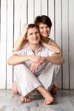 La giovane coppia sta abbracciando vicino alla parete di legno bianca Fotografia Stock Libera da Diritti