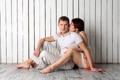 La giovane coppia sta baciando vicino alla parete di legno bianca Fotografie Stock