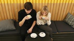 La giovane coppia sta bevendo il caffè e sta parlando mentre si sedeva al caffè Fotografia Stock